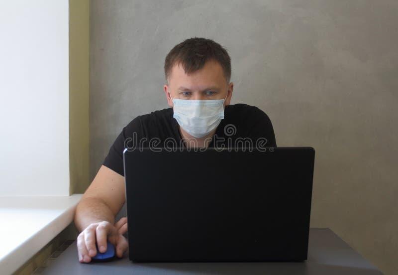 戴面罩的男子因检疫冠状病毒covid-19大流行而在家工作 带笔记本电脑的商务人员在家远程工作 免版税库存图片