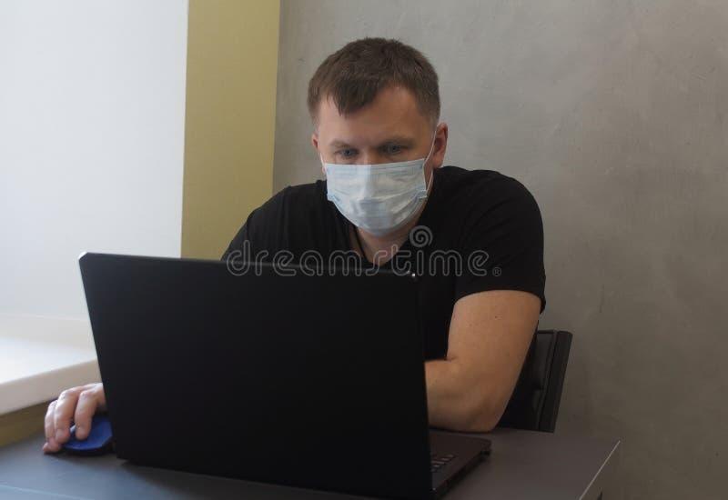 戴面罩的男子因检疫冠状病毒covid-19大流行而在家工作 带笔记本电脑的商务人员在家远程工作 免版税库存照片