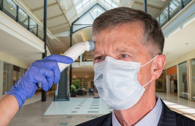 戴面罩的高级男子,在商店检查病毒 库存图片