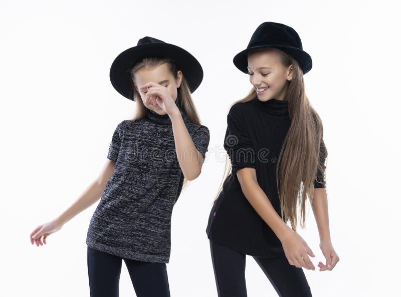 戴高领衫毛线衣、牛仔裤和帽子,微笑的跳舞的两位逗人喜爱的少年女朋友女小学生 在白色 方式 图库摄影