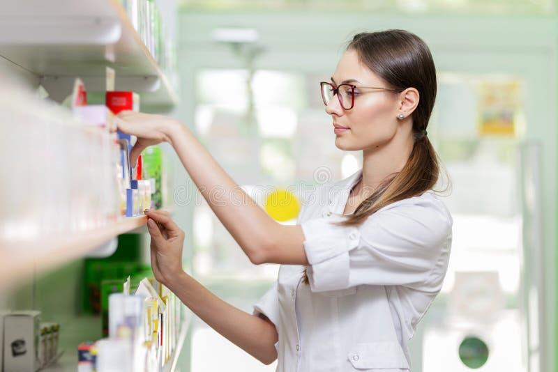 戴黑发和眼镜的一个逗人喜爱的稀薄的夫人,穿实验室外套,采取某事从在一家最新药房的架子 库存图片