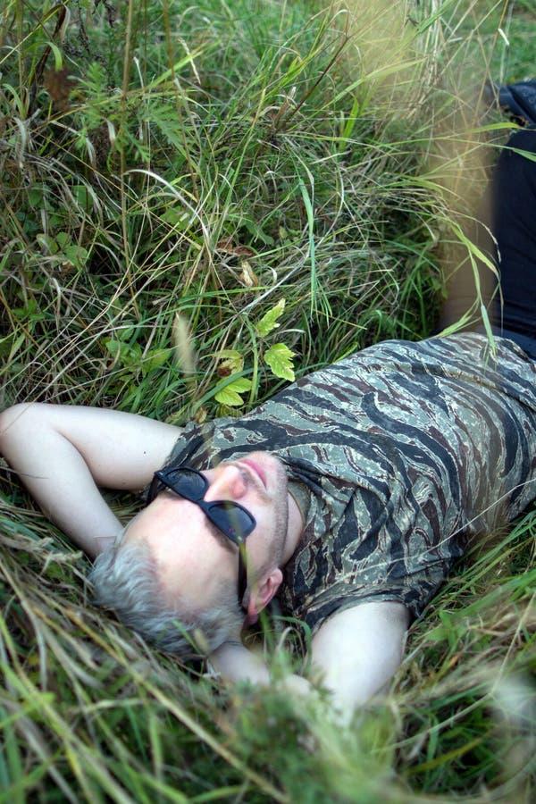 戴黑太阳镜的一个年轻英俊的有胡子的白肤金发的人说谎在草和查寻对天空 免版税库存图片