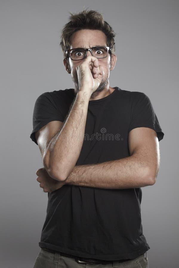 戴黑色眼镜的年轻人在一个灰色背景。 Sulphurated男孩 图库摄影