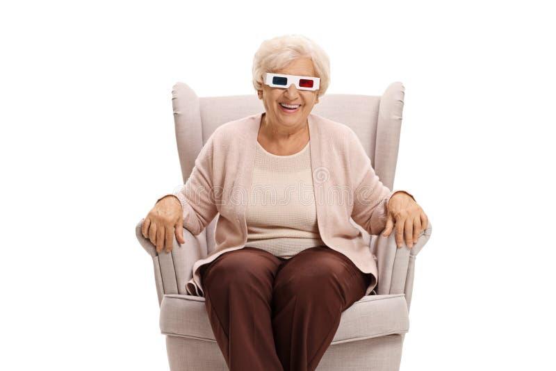 戴3D坐在扶手椅子的眼镜的年长妇女 库存照片