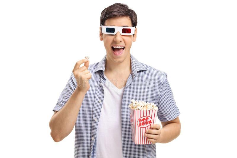戴3D有的眼镜的年轻人玉米花和笑 库存图片