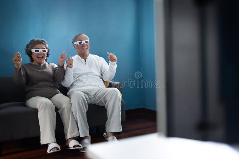 戴3D眼镜的快乐的亚洲资深夫妇 库存图片