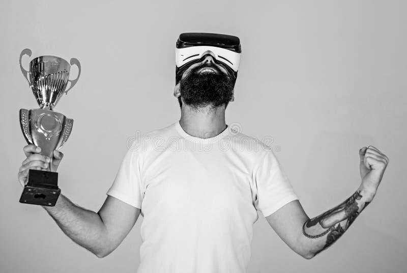 戴VR眼镜的人获得了冠军,举行手中金黄觚 有胡子的人在VR玻璃是优胜者,灰色 库存图片