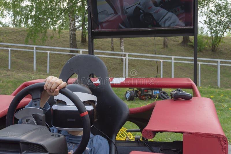 戴VR眼镜的孩子驾驶汽车 免版税库存图片