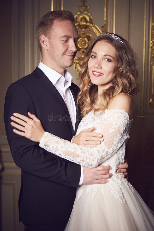 户内婚姻的夫妇互相拥抱 白色礼服的美丽的式样女孩 诉讼的人 有新郎的秀丽新娘 免版税库存照片