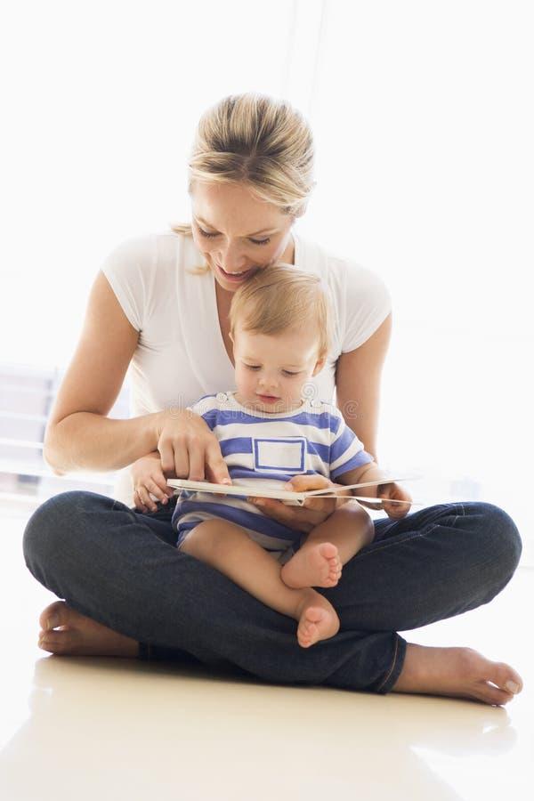 户内婴孩书照顾读取 免版税库存照片