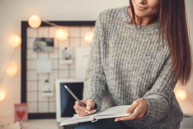 户内少妇自由职业者家庭办公室概念采取在计划者特写镜头的冬天大气笔记 免版税库存照片