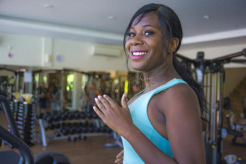 户内年轻有吸引力和愉快的黑非裔美国人的运动的妇女训练踏车连续锻炼健身房画象在fitne的 免版税库存照片