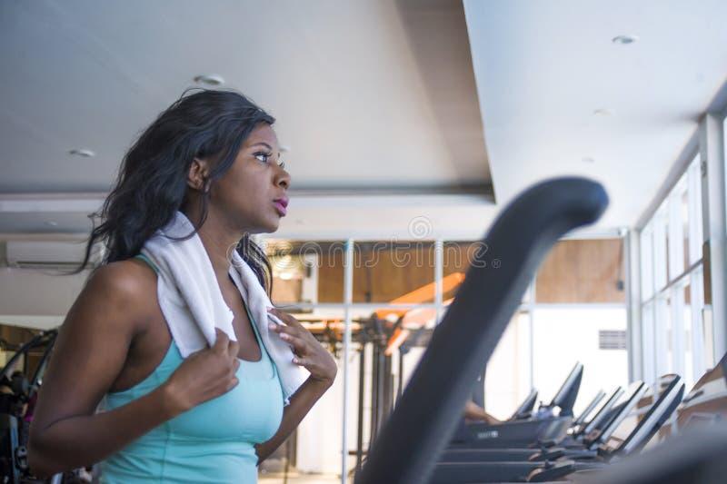 户内年轻有吸引力和美丽的黑美国黑人的运动的妇女训练踏车连续锻炼健身房画象在fitn的 免版税库存照片