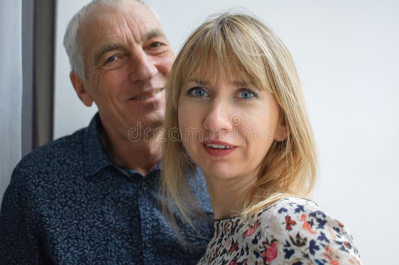 户内接近拥抱的年长人和他的年轻金发的妻子画象在他们自己的房子里面 库存图片