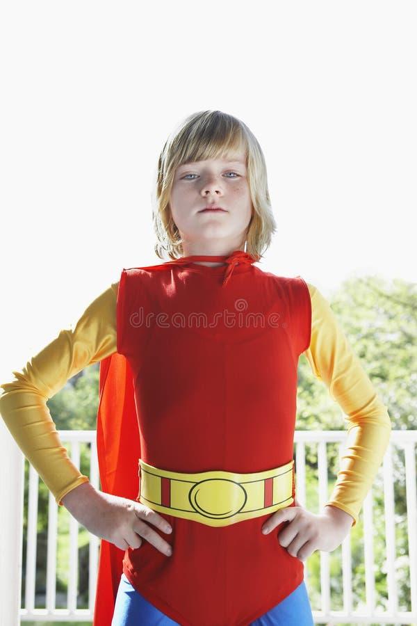 户内超级英雄服装的严肃的男孩 库存照片