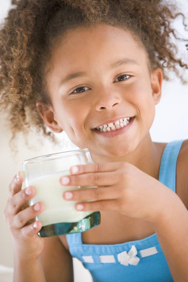户内饮用的女孩挤奶微笑的年轻人 免版税库存图片