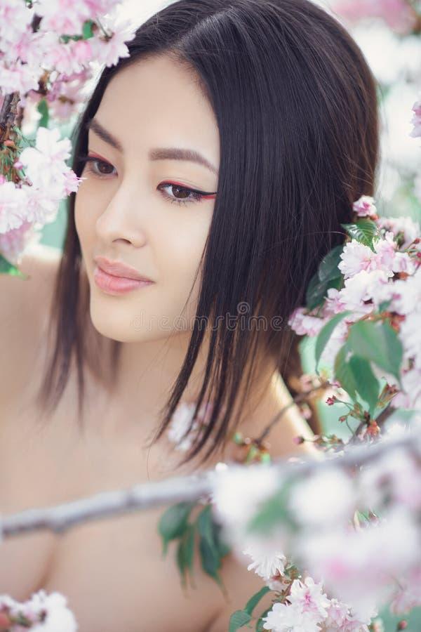 户外一个美好的幻想亚裔女孩的画象反对天然泉花背景 免版税库存图片