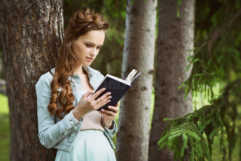 户外一本美丽的女孩阅读书的画象 图库摄影