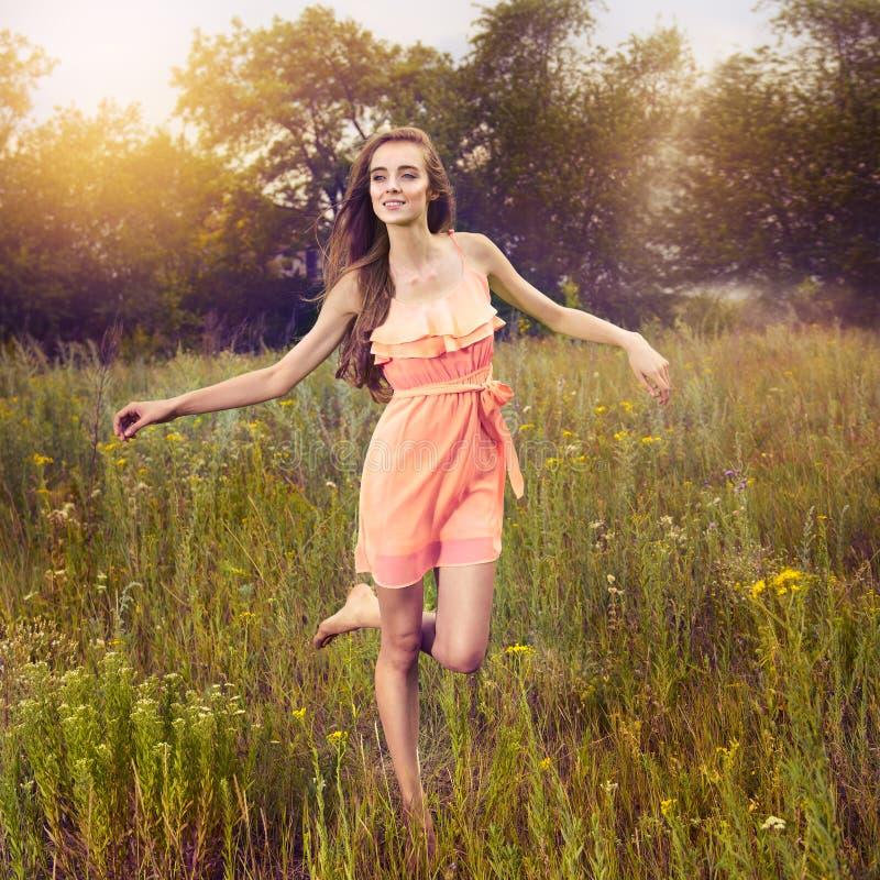 户外享受自然和赛跑在草甸的秀丽女孩 免版税库存照片