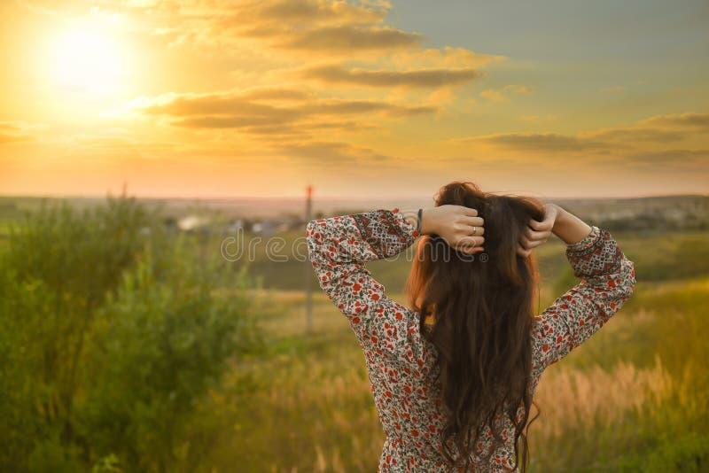 户外享受自然的秀丽女孩 与长的健康吹的头发运行在春天领域的,太阳的美好的模型 免版税库存图片