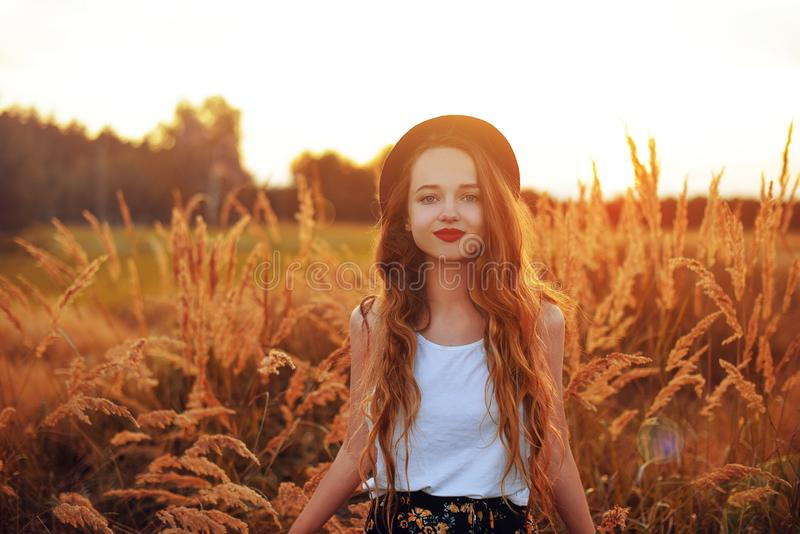 户外享受自然的秀丽女孩 相当在帽子运行在春天领域的,太阳光的少年模型 浪漫 免版税库存图片