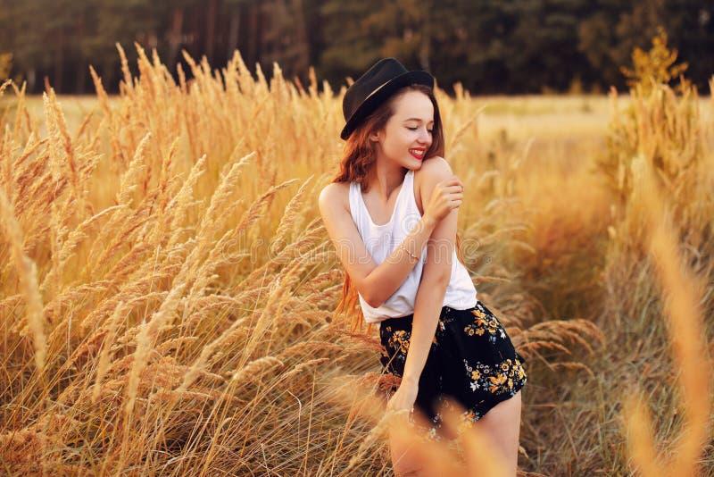 户外享受自然的秀丽女孩 相当在帽子运行在春天领域的,太阳光的少年模型 浪漫 图库摄影