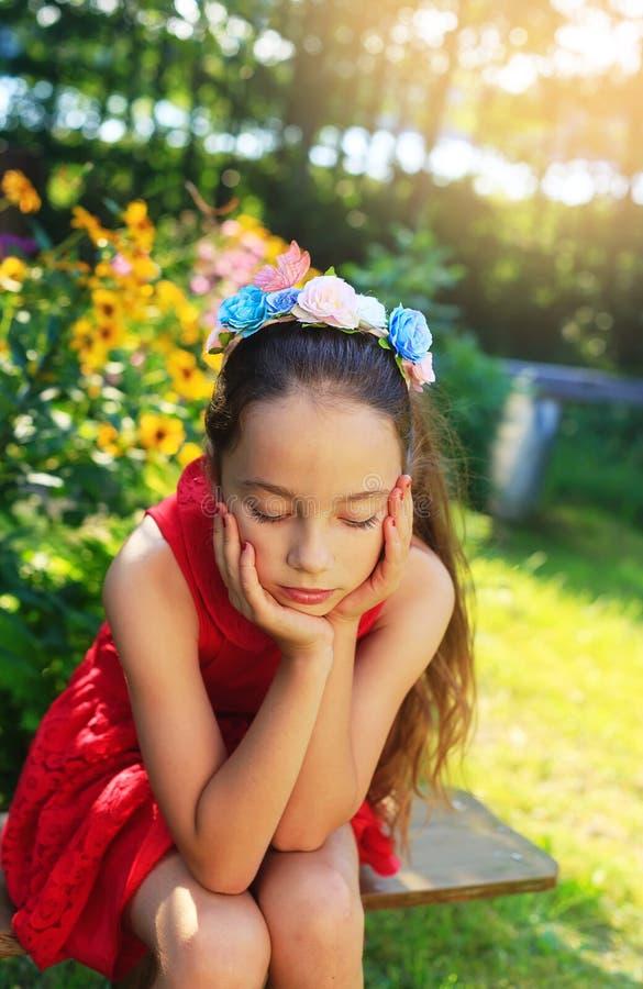 户外作梦在庭院的秀丽哀伤的女孩 美丽的Teena 库存图片