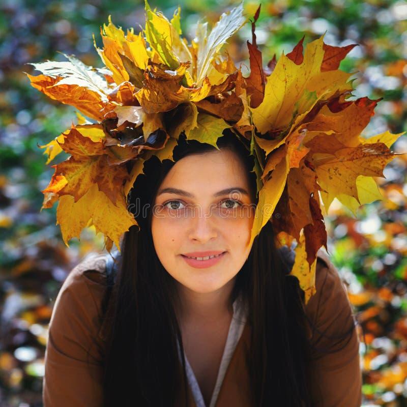 户外佩带秋叶的花圈迷人的年轻女人画象的生活方式关闭 走秋天 免版税库存图片