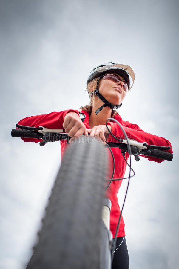 户外俏丽,年轻女性骑自行车的人在她的登山车 免版税图库摄影