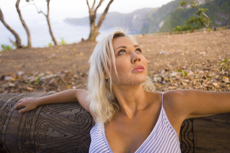 户外倾斜在树干的年轻美丽和轻松的白肤金发的妇女生活方式画象享受平安的自然围拢了 图库摄影