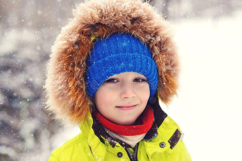 户外冬季衣服的逗人喜爱的儿童男孩 被点燃的画象愉快 免版税图库摄影