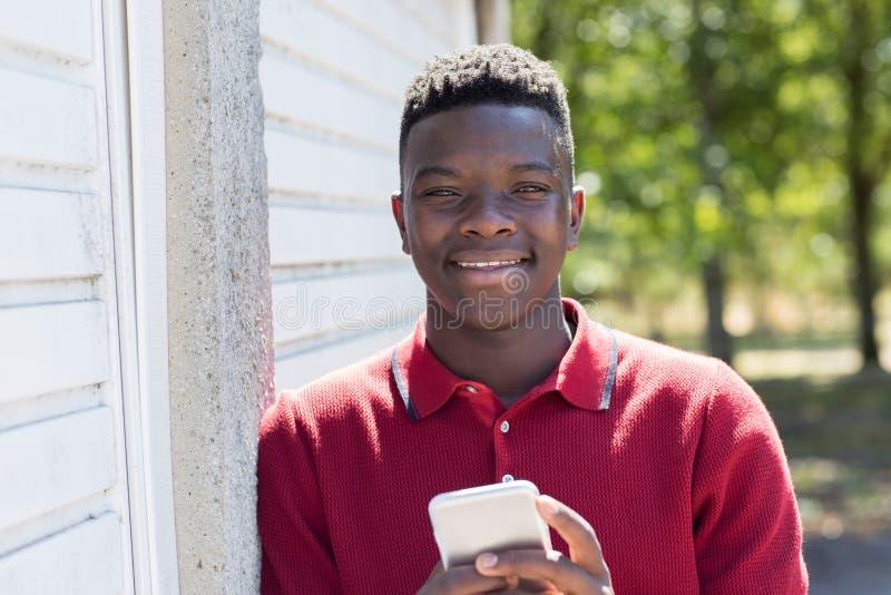 户外发正文消息的十几岁的男孩画象从MOBIL 免版税库存图片
