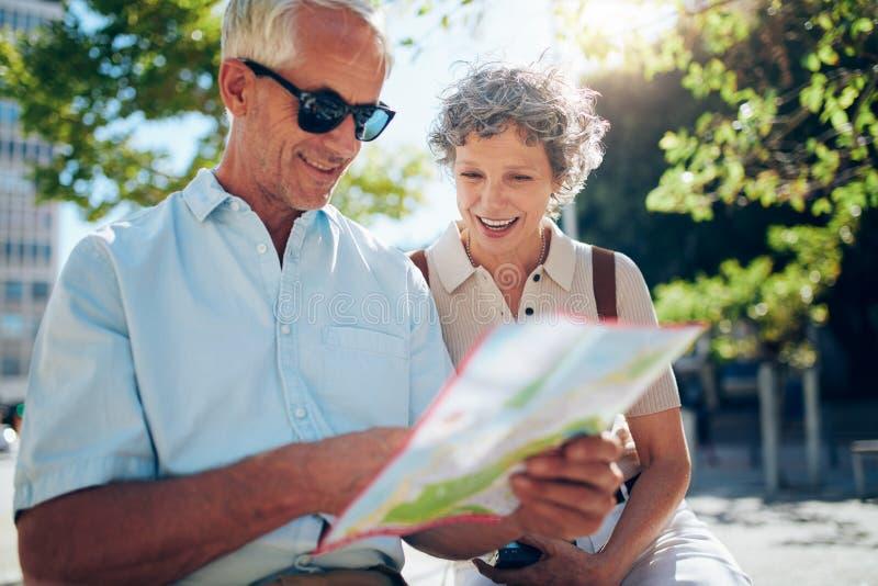 户外坐长凳和使用城市地图的年长夫妇 免版税图库摄影