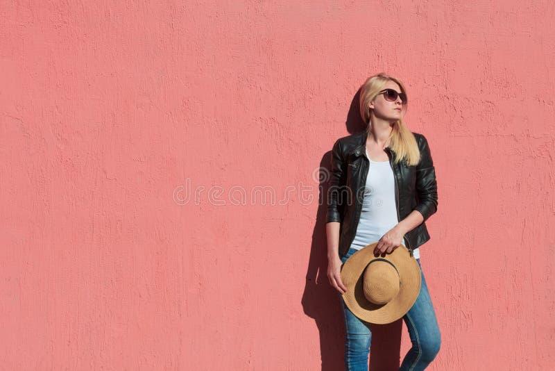 户外夏日照片:年轻金发女子身着黑色皮夹克,白色T恤上戴太阳镜,双手顶帽 库存照片