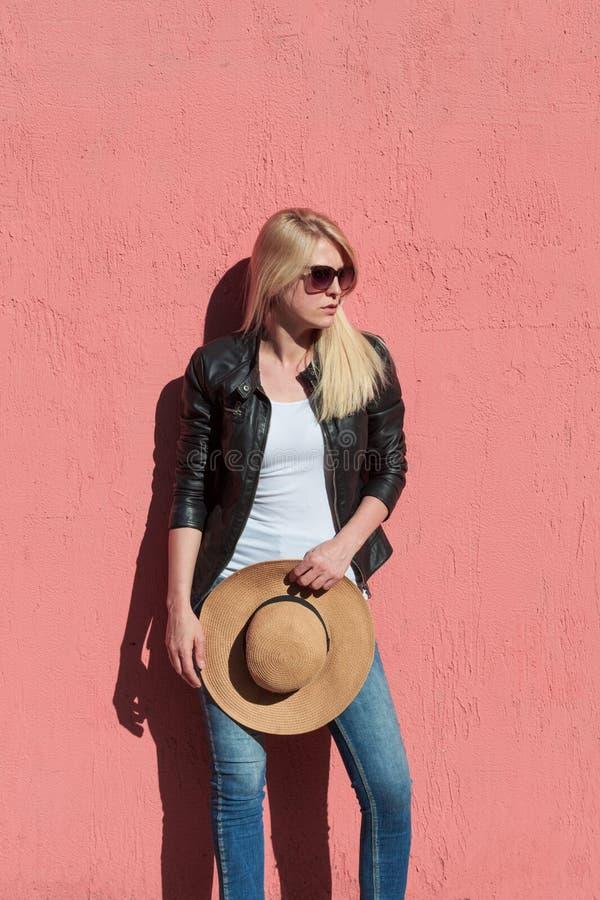 户外夏日照片:年轻金发女子身着黑色皮夹克,白色T恤上戴太阳镜,双手顶帽 免版税图库摄影