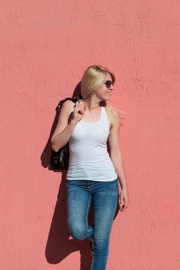 户外夏日照片:年轻金发女性开朗活泼,戴太阳镜,白色坦克顶在粉色墙模拟坦克顶 免版税图库摄影