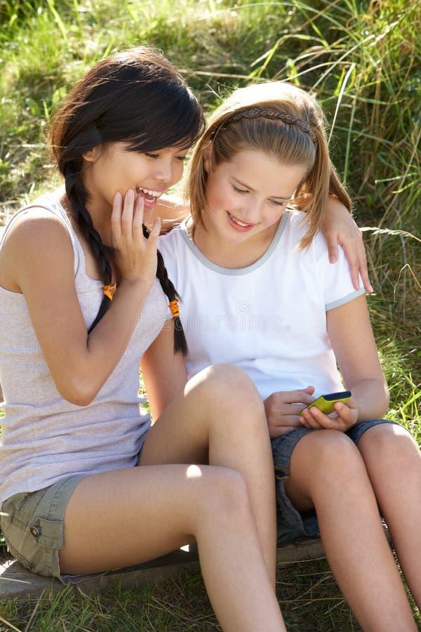 户外女孩给少年使用打电话 免版税库存照片