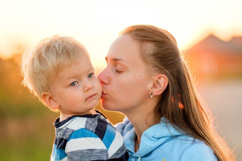 户外妇女和孩子在日落 她亲吻的母亲儿子 免版税图库摄影