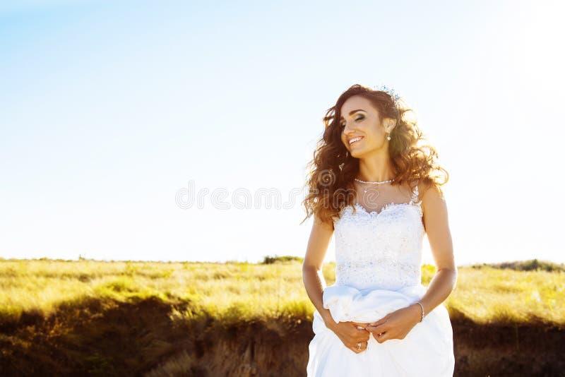户外婚礼礼服的少妇 一个领域的美丽的新娘在日落 库存图片