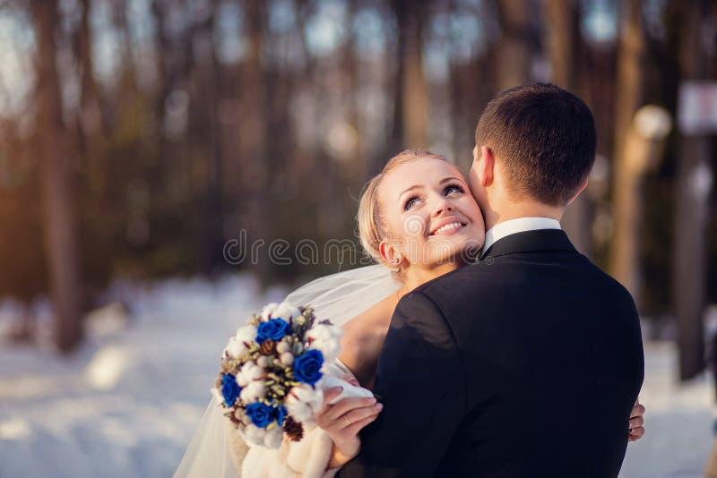 户外婚姻冬天的新娘新郎 美好的年轻夫妇在森林 免版税库存照片