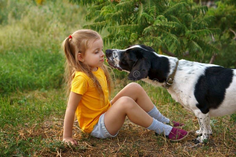 户外小女孩和杂种狗 免版税库存图片