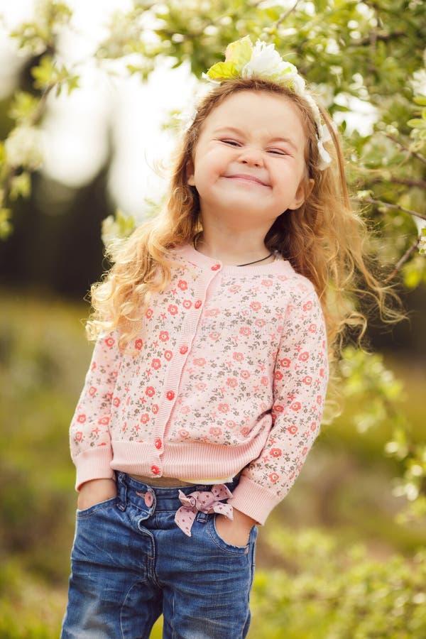 户外小女孩画象在一个繁茂花园里 库存图片