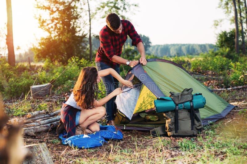 户外年轻夫妇安装帐篷,远足和野营 库存照片