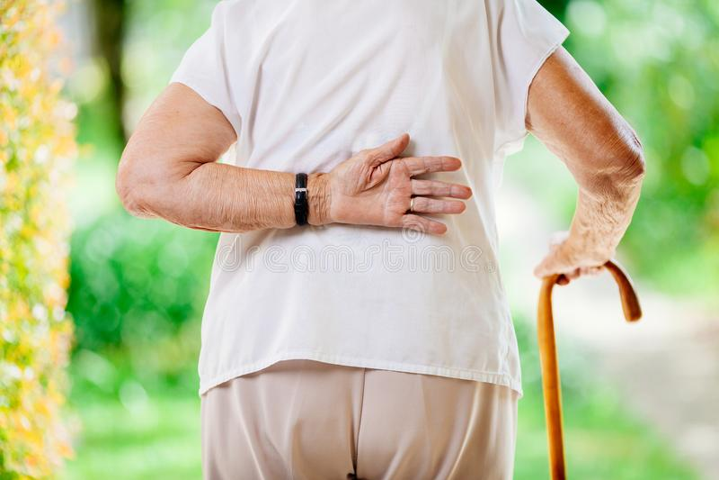 户外年长妇女充满背部疼痛 免版税库存照片