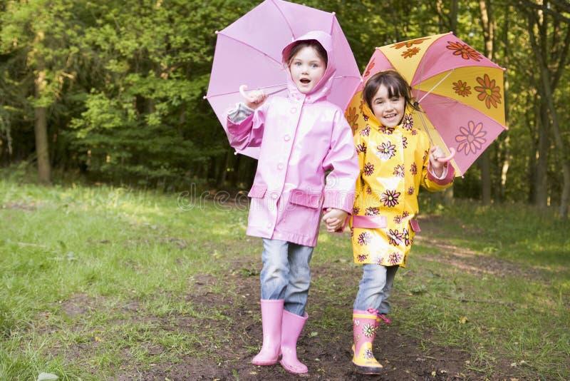 户外微笑的姐妹二把伞 免版税图库摄影