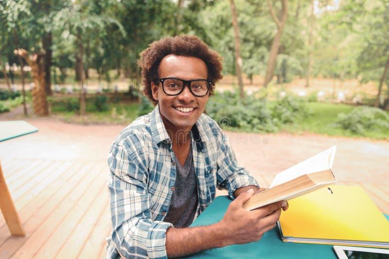 户外快乐的非洲年轻人阅读书 免版税库存照片