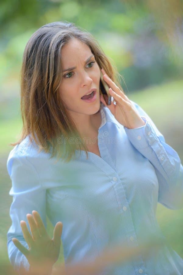 户外恼怒的妇女在手机 免版税库存照片