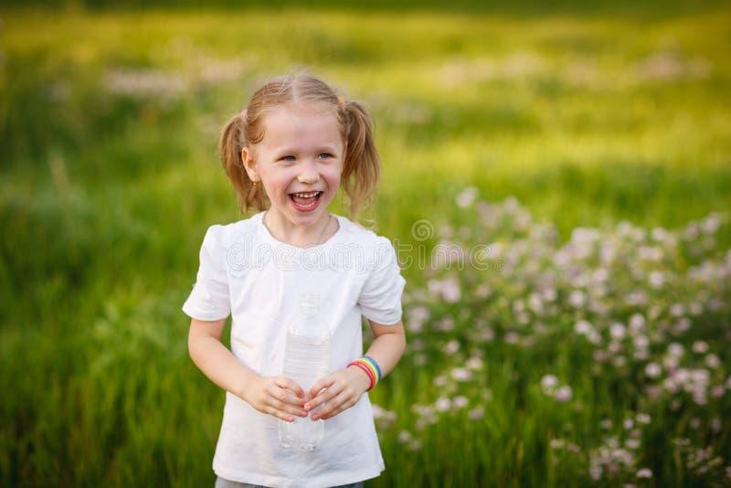 户外拿着瓶水的笑的女孩 库存图片