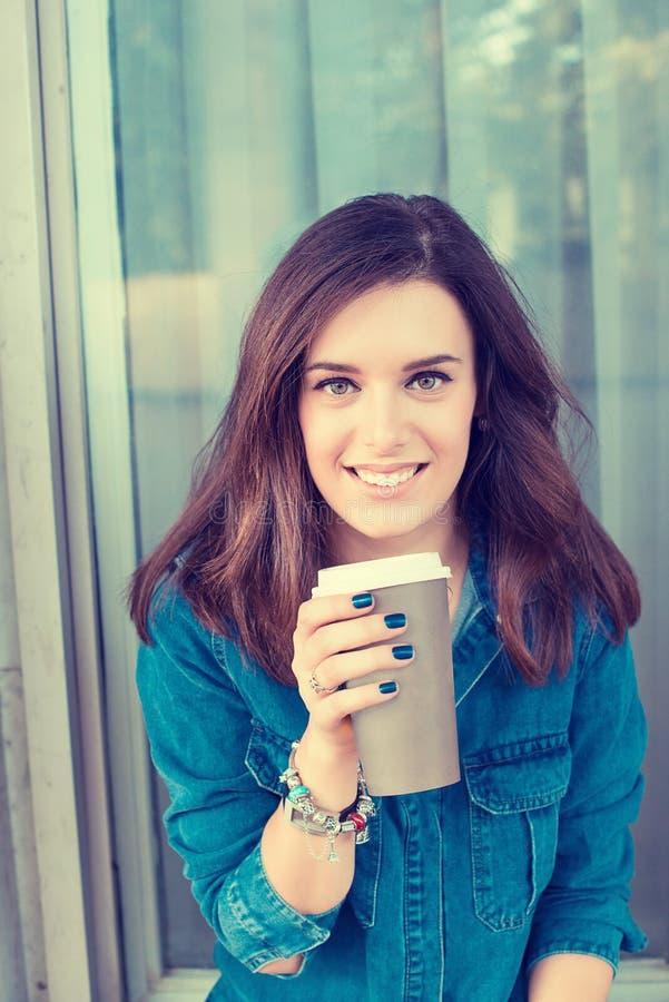 户外拿着纸杯的妇女饮用的咖啡 库存图片