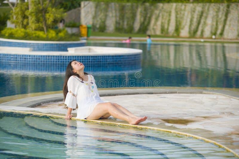 户外放松在热带手段游泳场的年轻愉快和美丽的亚裔韩国旅游妇女生活方式画象  免版税库存图片